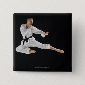 Young man performing karate kick on black 15 cm square badge