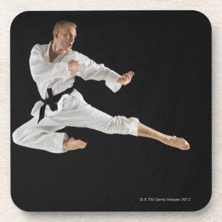 Young man performing karate kick on black beverage coasters