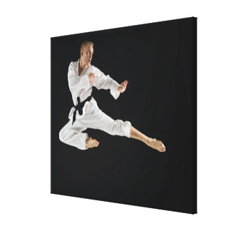 Young man performing karate kick on black canvas print