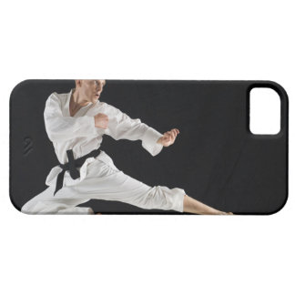 Young man performing karate kick on black case for the iPhone 5