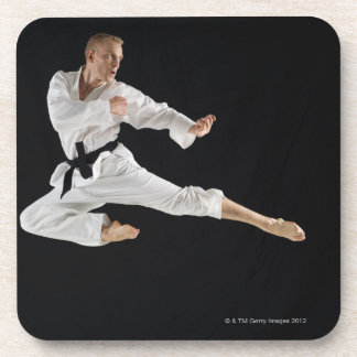 Young man performing karate kick on black coaster