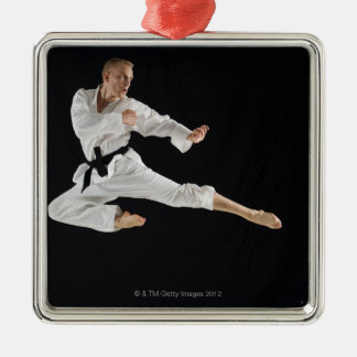 Young man performing karate kick on black Silver-Colored square decoration