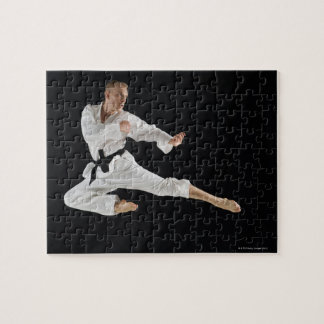 Young man performing karate kick on black jigsaw puzzle