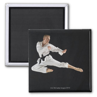 Young man performing karate kick on black magnet