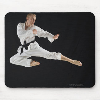 Young man performing karate kick on black mouse mat