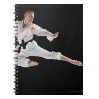 Young man performing karate kick on black notebook