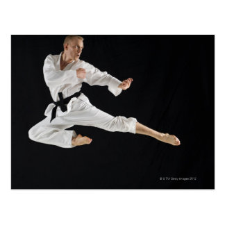 Young man performing karate kick on black postcard