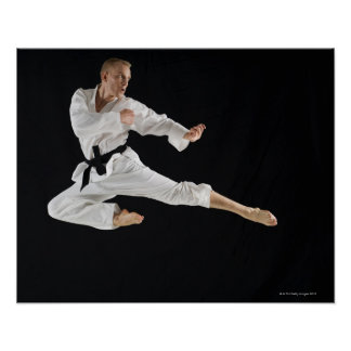 Young man performing karate kick on black poster