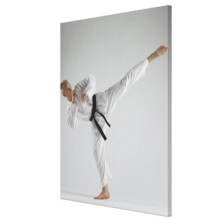 Young man performing karate kick on white canvas print