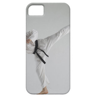 Young man performing karate kick on white case for the iPhone 5
