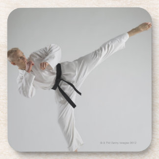 Young man performing karate kick on white coaster