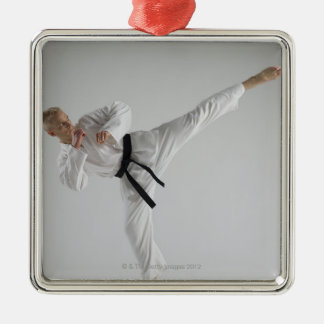 Young man performing karate kick on white Silver-Colored square decoration