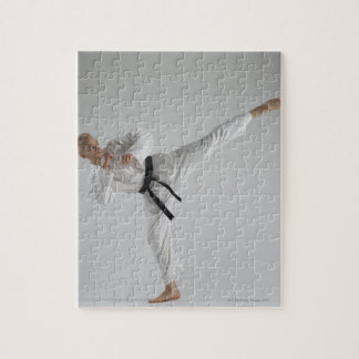 Young man performing karate kick on white jigsaw puzzle