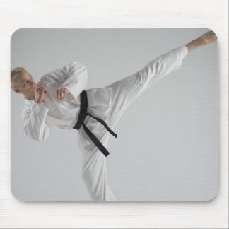 Young man performing karate kick on white mouse mat