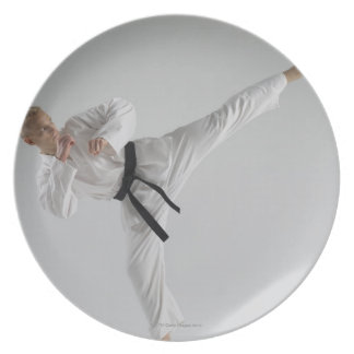 Young man performing karate kick on white plate