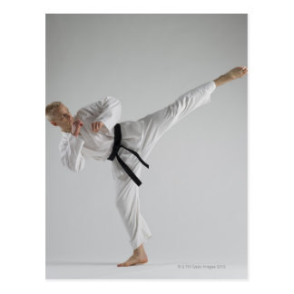 Young man performing karate kick on white postcard