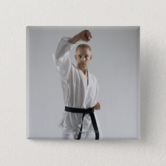 Young man performing karate stance on white 15 cm square badge