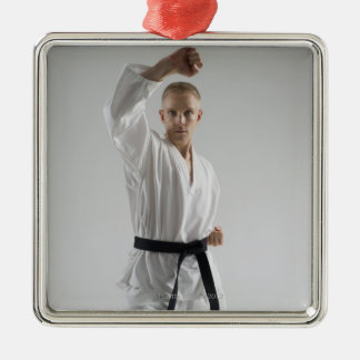 Young man performing karate stance on white christmas ornament