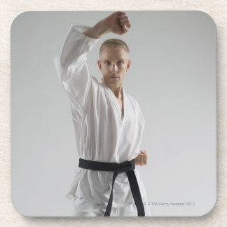 Young man performing karate stance on white coaster