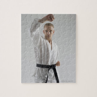 Young man performing karate stance on white jigsaw puzzle