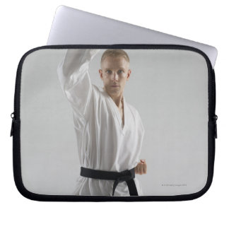 Young man performing karate stance on white laptop sleeve