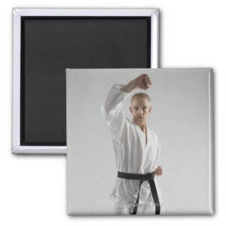 Young man performing karate stance on white magnet