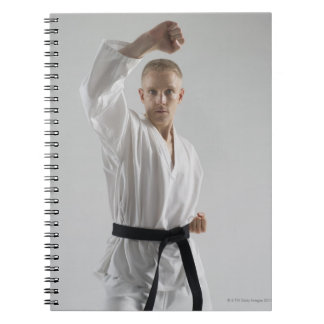 Young man performing karate stance on white spiral notebook