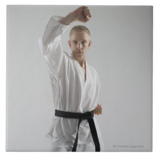 Young man performing karate stance on white tile