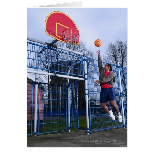 Young man playing basketball outdoors cards