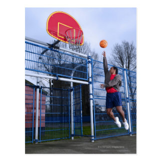 Young man playing basketball outdoors postcard