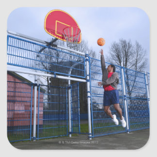 Young man playing basketball outdoors square sticker
