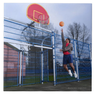 Young man playing basketball outdoors tile