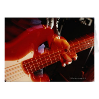 Young man playing bass guitar, close-up of hand card