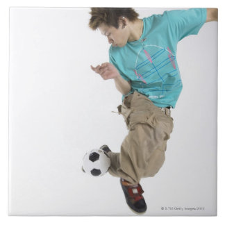 Young man playing soccer tile