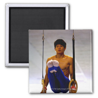 Young man practicing gymnastic rings magnet