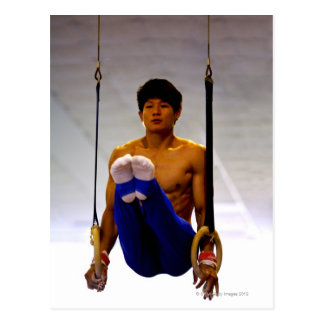 Young man practicing gymnastic rings postcard