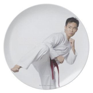 Young man practicing side kick party plates