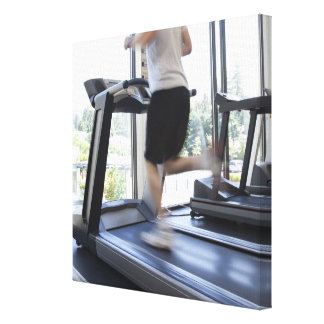 Young man running on a treadmill at health club, stretched canvas prints