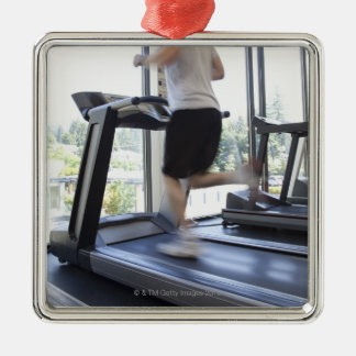 Young man running on a treadmill at health club, christmas ornament