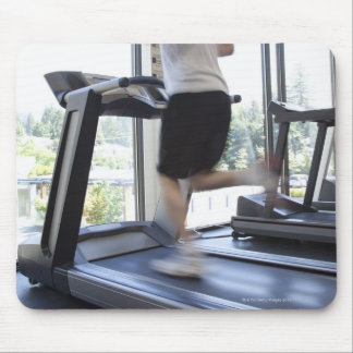 Young man running on a treadmill at health club, mouse pad