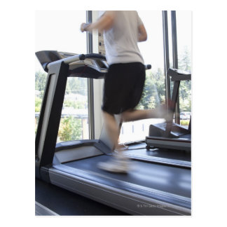 Young man running on a treadmill at health club, postcard
