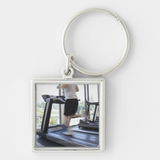 Young man running on a treadmill at health club, Silver-Colored square key ring