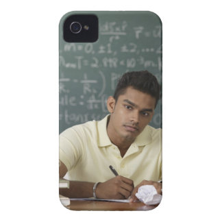young man sitting at his desk, writing Case-Mate iPhone 4 cases