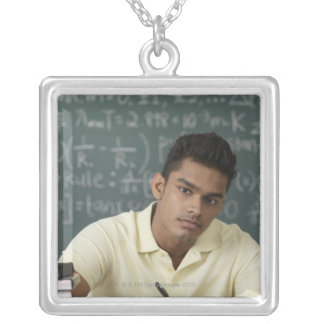 young man sitting at his desk, writing silver plated necklace