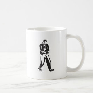 young man talking on a cell phone  while walking coffee mug