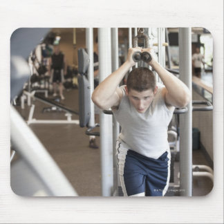 Young man working out his triceps on a cable mouse mat