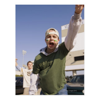 Young men cheering in parking lot before game postcard