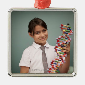 Young schoolgirl holds a colorful model christmas ornament