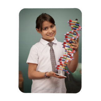 Young schoolgirl holds a colorful model rectangular photo magnet