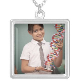 Young schoolgirl holds a colorful model silver plated necklace